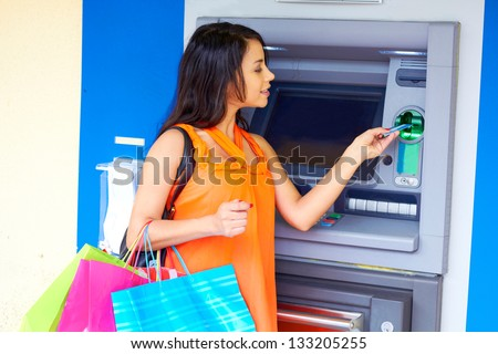Portrait of an ecstatic young woman carrying colored shopping bags. Vertical shot. - stock photo