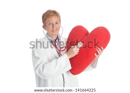 portrait of an elder female doctor of cardiology holding a red heart and red stethoscope, wearing a white lab coat, explaining - stock photo