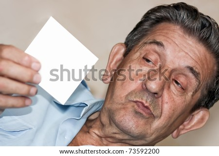 portrait of an elderly amusing man holds empty white blank - stock photo