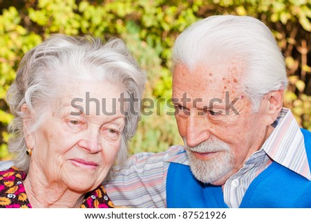 Portrait of an elderly couple sitting outdoors. - stock photo