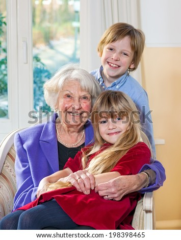 Portrait of an elderly grandmother and her grandchildren sitting in an armchair with the little girl on her lap while her young brother stands behind all looking at the camera with lovely happy smiles - stock photo