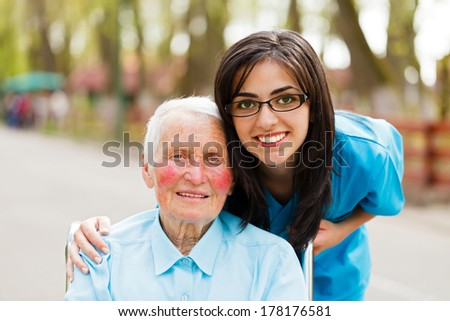 Portrait of an elderly lady and a kind nurse. - stock photo