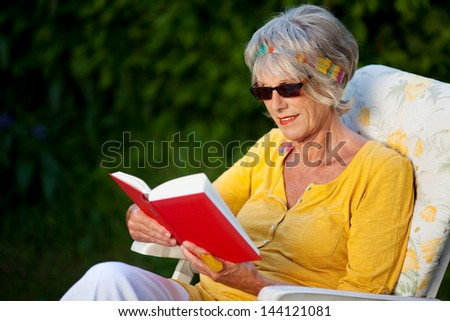 portrait of an elderly lady reading a book with sunglasses - stock photo