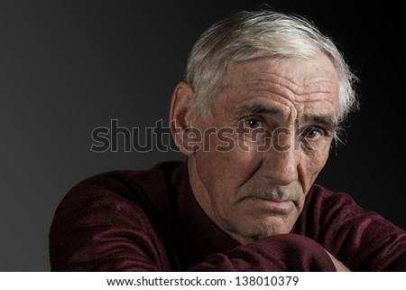 portrait of an elderly man on dark background - stock photo