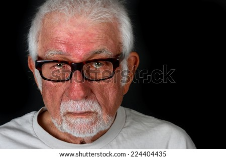 Portrait of an elderly man showing a sad expression with a tear coming down his cheek - stock photo