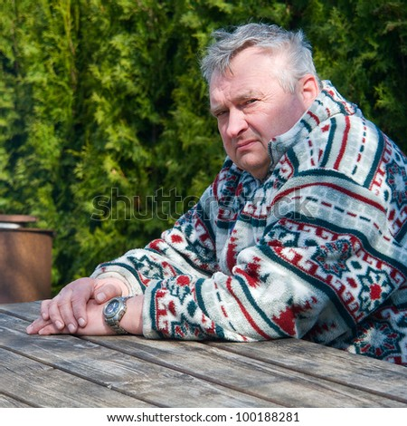 Portrait of an elderly man sitting at a wooden table in the park - stock photo