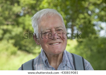Portrait of an elderly man smiling to camera with a lush green blurred countryside background in the South of England.