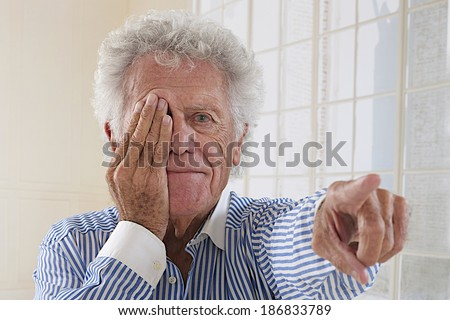 Portrait of an elderly  man taking eyesight test isolated on white background - stock photo