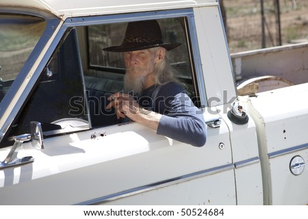 Portrait of an elderly man with a cowboy hat and white beard, driving a pickup truck and staring out the window. He is holding a cigarette and looking at the camera. Horizontal format. - stock photo