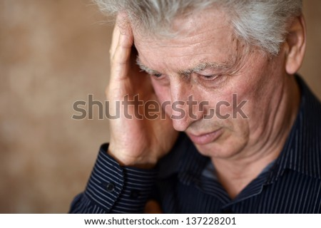 portrait of an elderly man with a headache on a beige background