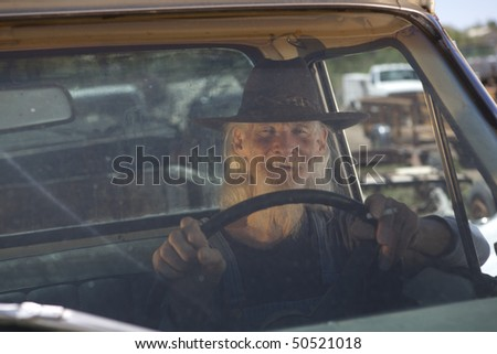 Portrait of an elderly man with a white beard and cowboy hat driving a pickup truck and looking out the windshield at the camera. Horizontal format. - stock photo