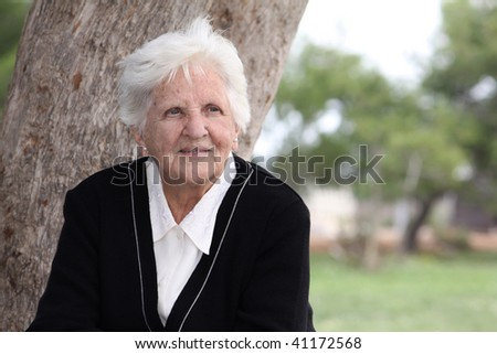 portrait of an elderly octogenarian sitting in the park - stock photo