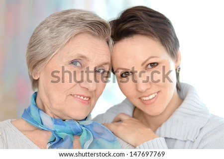 Portrait of an elderly woman and a young woman at home - stock photo