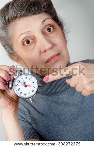 Portrait of an elderly woman anxiously pointing at the clock - stock photo
