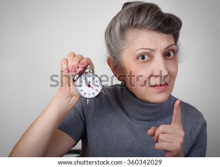 Portrait of an elderly woman holding a clock concept of time is running out - stock photo