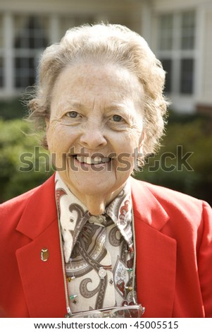 Portrait of an elderly woman in a red coat smiling towards the camera.  Vertical shot. - stock photo