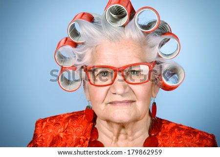 Portrait of an elderly woman in curlers looking at camera.