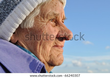 Portrait of an elderly woman, lost in thought, watching the distance, blue sky background