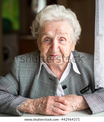 Portrait of an elderly woman sitting at the table. - stock photo