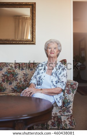 Portrait of an elderly woman sitting on a couch at old age home. Caucasian woman sitting on a sofa and looking at camera. - stock photo