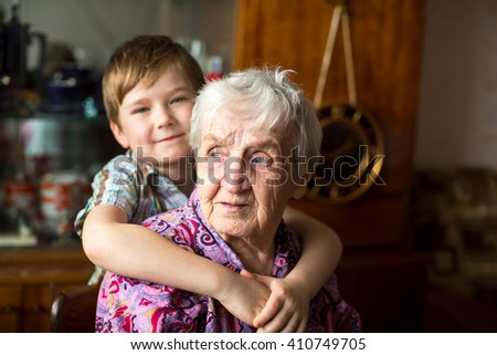 Portrait of an elderly woman with a small grandson in the background. - stock photo