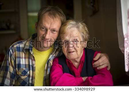 Portrait of an elderly woman with her adult grandson. - stock photo