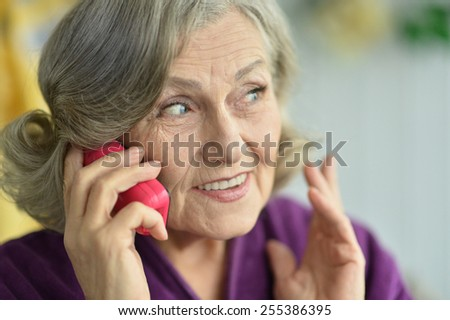 Portrait of an elderly woman with phone - stock photo