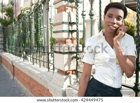 Portrait of an elegant african american business woman in a classic city with iron fence, using a smart phone on phone call conversation, smiling outdoors. Black professional woman using technology. - stock photo