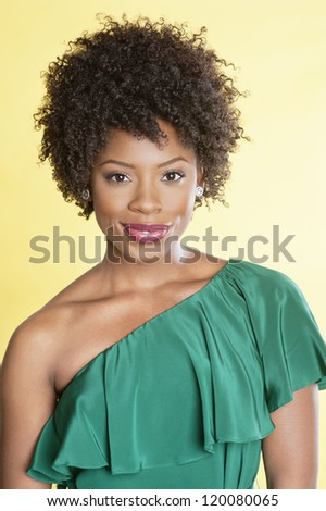 Portrait of an elegant African American in an off shoulder dress smiling over colored background - stock photo