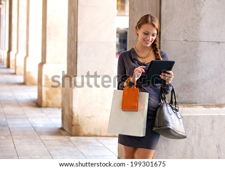 Portrait of an elegant and attractive young woman with shopping bags using a digital tablet while in a city with columns aligned during a sunny day. Consumer and technology lifestyle, outdoors. - stock photo
