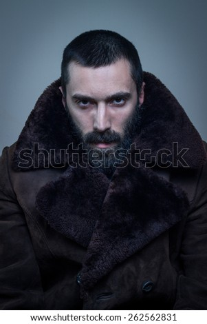 Portrait of an elegant bearded man in a fur coat. Very fashionable. - stock photo