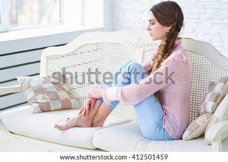 Portrait of an elegant beautiful young woman daydreaming on a vintage sofa