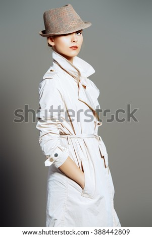 Portrait of an elegant fashion model posing at studio in a coat and hat. Beauty, fashion. Business style. - stock photo