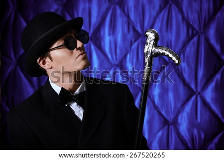 Portrait of an elegant old-fashioned artist man wearing black suit and bowler-hat. Fashion, style. Cinema, theater. - stock photo