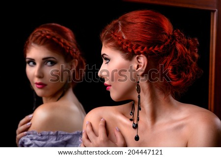 Portrait of an elegant redhead woman looking in the mirror - stock photo