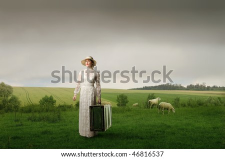 Portrait of an elegant woman carrying an old suitcase on a green meadow - stock photo