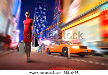 Portrait of an elegant woman carrying some shopping bags standing on a catwalk of a city street - stock photo