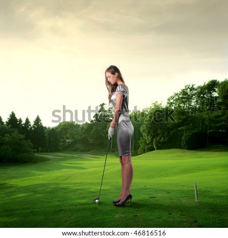 Portrait of an elegant woman playing golf on a green woman - stock photo
