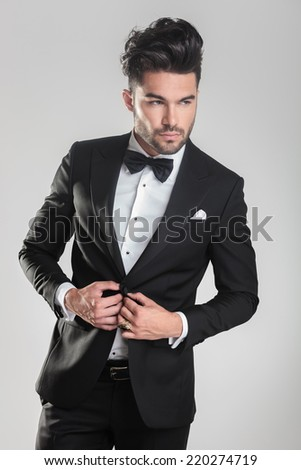 portrait of an elegant young man in tuxedo closing his jacket while looking away from the camera - stock photo