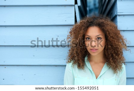 Portrait of an elegant young woman against blue wall - stock photo