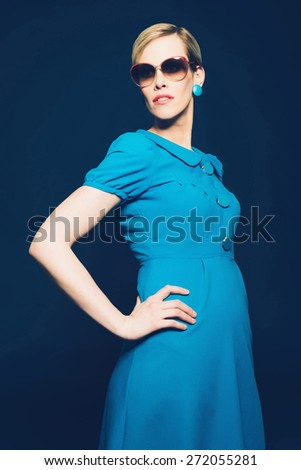Portrait of an Elegant Young Woman Posing in Blue Full Dress with Sunglasses, Looking to the Left with Hand on her Hips, Isolated on Dark Blue Background. - stock photo