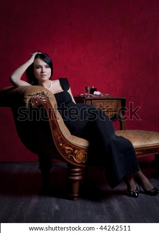 Portrait of an elegantly beautiful young woman posing on an antique couch - stock photo