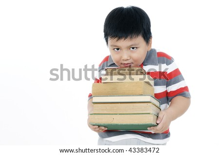 Portrait of an elementary schoolboy carrying a heavy pile of books on white background.