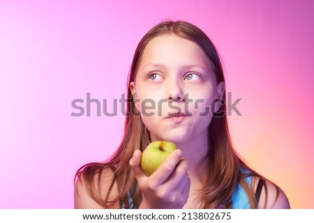Portrait of an emotional funny teen girl eating apple - stock photo