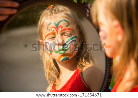 Portrait of an emotional girl with paint on his face looks in the mirror - stock photo
