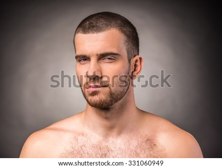 Portrait of an emotional young man with a naked torso on a black background