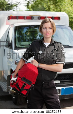 Portrait of an EMS professional carrying a protable oxygen unit - stock photo