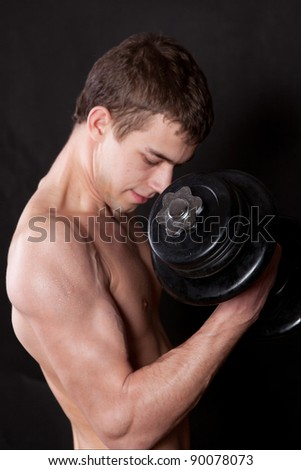 Portrait of an energetic naked man lifting dumbbell against black background - stock photo