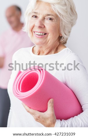 Portrait of an energetic senior woman holding a pink exercise mat and smiling cheerfully at the camera - stock photo
