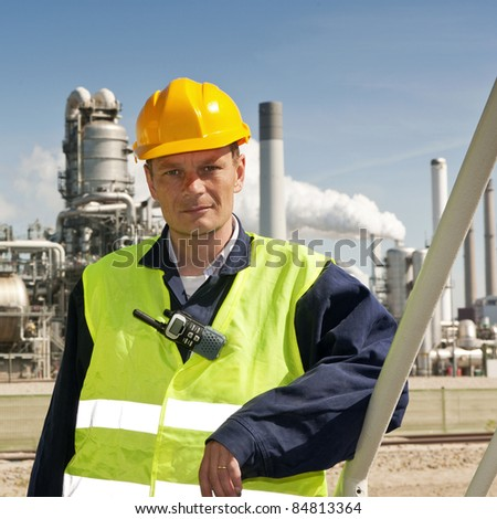 Portrait of an engineer in front of a petrochemical industry, with fire retardant clothing and a CB-radio clipped to a safety vest - stock photo
